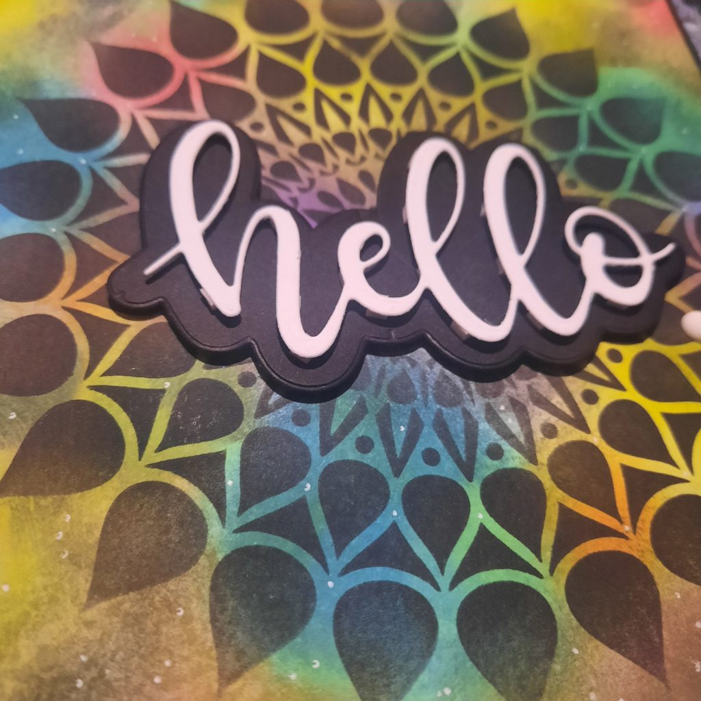 Hello sentiment on a colourful mandala stencilled background.
